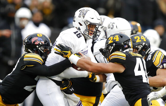 Northwestern quarterback Clayton Thorson (18) is sacked by Iowa's Amani Hooker, left, and Jack Hockaday, right, during the first half of an NCAA college football game, Saturday, Nov. 10, 2018, in Iowa City, Iowa. (AP Photo/Charlie Neibergall)