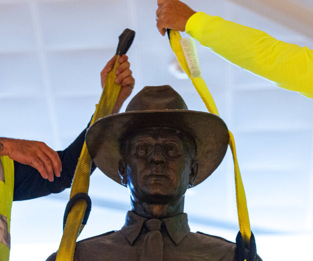 "A Phoenix 1 Restoration & Construction crew removes a 12-foot-tall bronze statue of a Texas Ranger, called ""One Riot, One Ranger,""  from the main lobby inside Love Field airport on Thursday, June 4, 2020 in Dallas. A published account of brutal and racist chapters in the history of an elite Texas investigative agency prompted Dallas officials to remove the statue from Love Field's passenger terminal that honored the agency. (Juan Figueroa/ The Dallas Morning News via AP)"