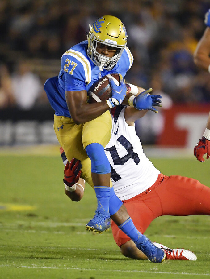 UCLA running back Joshua Kelley, left, runs the ball as Arizona defensive end Kylan Wilborn tries to tackle him during the first half of an NCAA college football game, Saturday, Oct. 20, 2018, in Pasadena, Calif. (AP Photo/Mark J. Terrill)