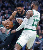 Minnesota Timberwolves center Karl-Anthony Towns, left, grimaces as he collides with Boston Celtics forward Marcus Morris (13) during the first quarter of an NBA basketball game in Boston, Wednesday, Jan. 2, 2019. (AP Photo/Charles Krupa)