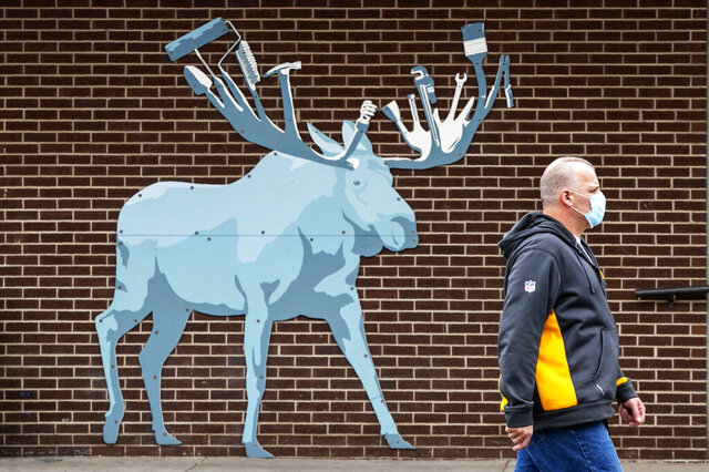 A customer leaves the Maine Hardware store where an artistic rendition of a moose, the state animal, decorates an outside wall, Friday, May 15, 2020, in Portland, Maine. Another 38 people tested positive for the new coronavirus but there were no deaths in the previous 24 hours, the Maine Center for Disease Control reported Friday. (AP Photo/Robert F. Bukaty)