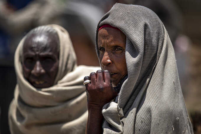 FILE - In this Saturday, May 8, 2021, file photo, a woman waits to receive foodstuffs such as wheat, yellow split peas and vegetable oil at a food distribution operated by the Relief Society of Tigray in the town of Agula, in the Tigray region of northern Ethiopia. The U.N. humanitarian chief warned Friday, June 4, 2021, that famine is imminent in Ethiopia's embattled Tigray region and the country's north and there is a risk that hundreds of thousands of people or more will die. (AP Photo/Ben Curtis, File)