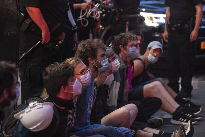 Protesters who were arrested by police for breaking a curfew during a solidarity rally calling for justice over the death of George Floyd, sit on a sidewalk as they wait to be taken away in a van on Thursday, June 4, 2020, in New York. Floyd, an African American man, died on May 25 after a white Minneapolis police officer pressed a knee into his neck for several minutes even after he stopped moving and pleading for air. (AP Photo/Wong Maye-E)