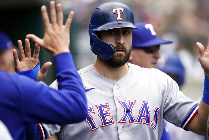 Texas Rangers designated hitter Joey Gallo is greeted in the dugout after scoring during the fourth inning of a baseball game against the Detroit Tigers, Thursday, July 22, 2021, in Detroit. (AP Photo/Carlos Osorio)