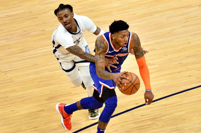 New York Knicks guard Elfrid Payton handles the ball against Memphis Grizzlies guard Ja Morant in the second half of an NBA basketball game Monday, May 3, 2021, in Memphis, Tenn. (AP Photo/Brandon Dill)