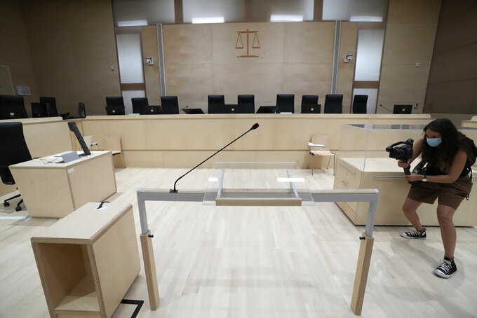 A woman videos the specially built courtroom Thursday, Sept. 2 2021 at the court house in Paris. In an enormous custom-designed chamber, France is putting on trial 20 men accused in the Nov. 13, 2015, Islamic State terror attacks on Paris that left 130 people dead and hundreds injured. Nine gunmen and suicide bombers struck within minutes of each other at the national soccer stadium, the Bataclan concert hall and restaurants and cafes. Salah Abdeslam, the lone survivor of the terror cell from that night is among those being tried for the deadliest attack in France since World War II. (AP Photo/Francois Mori)