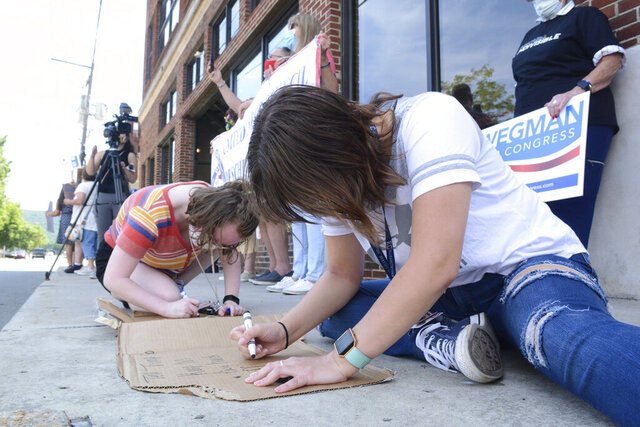 Chelsea Balulis, of Pottsville, front, and Ashlee Reick, of Auburn, make signs at a rally hosted by Todd Zimmerman and Schuylkill Democratic Action Group to support the United States Postal Service along Progress Avenue, Thursday, Aug. 20, 2020, in Pottsville, Pa., in front of U.S. Rep. Dan Meuser's, R-Penn., office. Attendees were encouraged to buy a book of forever stamps to support the post office. (Lindsey Shuey/Republican-Herald via AP)
