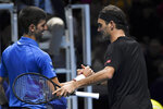 Roger Federer of Switzerland, right, and Novak Djokovic of Serbia shake hands after winning the match point during their ATP World Tour Finals singles tennis match at the O2 Arena in London, Thursday, Nov. 14, 2019. (AP Photo/Alberto Pezzali)