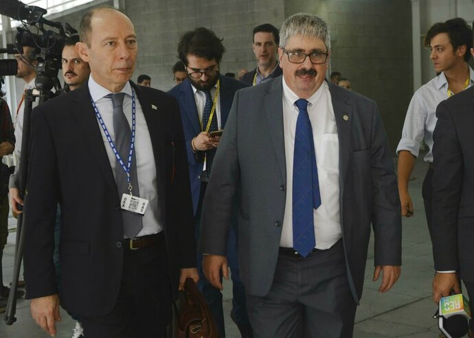 Uruguay's Deputy Foreign Minister Ariel Bergamino, right, leaves the session of the 49th OAS General Assembly in Medellin, Colombia, Thursday, June 27, 2019. Bergamino walked out, leading a protest over the participation of diplomats appointed by Venezuelan opposition leader Juan Guaidó. (AP Photo/Luis Benavides)