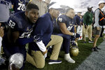 Navy head coach Ken Niumatalolo, center, kneel with defensive end Denzel Polk (52) and defensive lineman Jackson Pittman (99) as they watch the final play of an NCAA college football game against Air Force Saturday, Oct. 5, 2019, in Annapolis, Md. Navy won 34-25. (AP Photo/Julio Cortez)