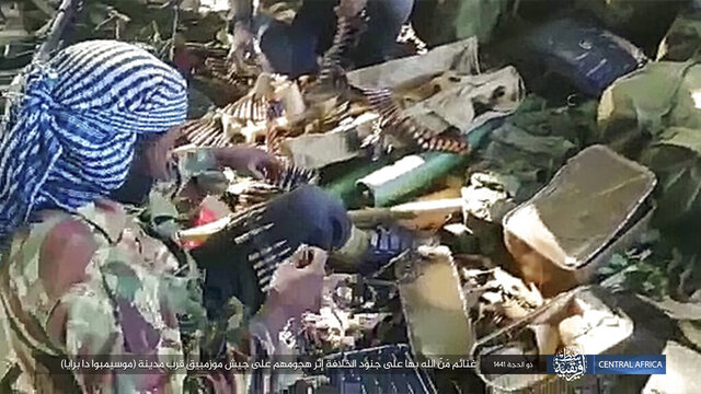 This image distributed online by the Islamic State Central Africa Province (ISCAP) and provided by SITE Intelligence Group shows ISCAP fighters and weapons following clashes with Mozambican government troops on Thursday, Aug. 6, 2020, near Mocimboa da Praia, in northern Mozambique. The stinging success of Mozambique's Islamic extremist rebels in seizing and holding the northern port city signals to the government, neighboring countries and the world that Africa has yet another insurgency hotspot. Writing in Arabic reads