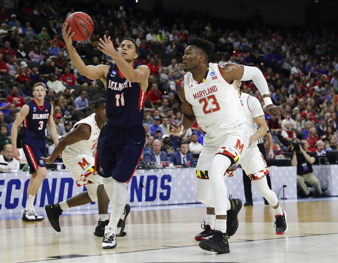 Belmont 's Kevin McClain (11) goes up for a shot over Maryland 's Bruno Fernando (23) during the first half of a first round men's college basketball game in the NCAA Tournament in Jacksonville, Fla., Thursday, March 21, 2019. (AP Photo/John Raoux)