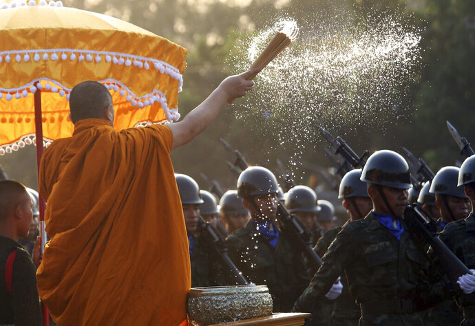 A Buddhist monk splashes holy water to Thai soldiers during the Royal Thai Armed Forces Day ceremony at a military base in Bangkok, Thailand, Friday, Jan. 18, 2019. (AP Photo/Sakchai Lalit)