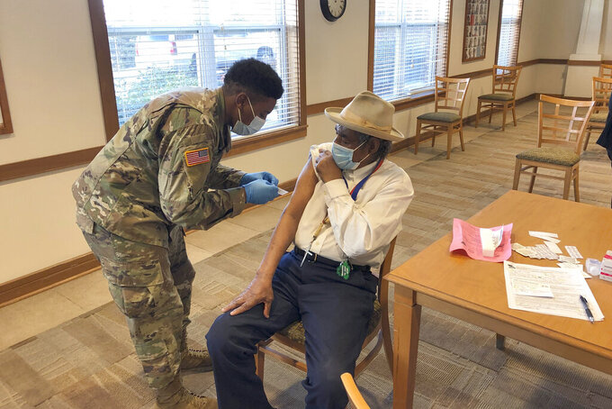 The Rev. Oliver Savage gets a COVID-19 vaccine from Missouri National Guard member Richard Waithira on Thursday, March 4, 2021, during a vaccination clinic at a St. Louis senior center.  Gov. Mike Parson visited the event. (AP Photo by Jim Salter)