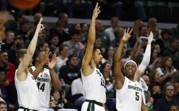 Michigan State forward Kyle Ahrens, left, forward Nick Ward (44), forward Kenny Goins (25) and guard Cassius Winston (5) react after a teammate's three-point basket during the second half of an NCAA college basketball game against Northern Illinois, Saturday, Dec. 29, 2018, in East Lansing, Mich. (AP Photo/Carlos Osorio)