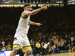 Iowa's Luka Garza points to the bench after dunking the ball against Penn State during the second half of an NCAA college basketball game, Saturday, Feb. 29, 2020, in Iowa City, Iowa. (AP Photo/Cliff Jette)
