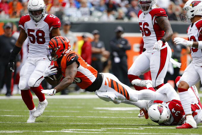 Cincinnati Bengals running back Joe Mixon (28) is tackled by Arizona Cardinals defensive back Jalen Thompson (34) in the first half of an NFL football game, Sunday, Oct. 6, 2019, in Cincinnati. (AP Photo/Frank Victores)