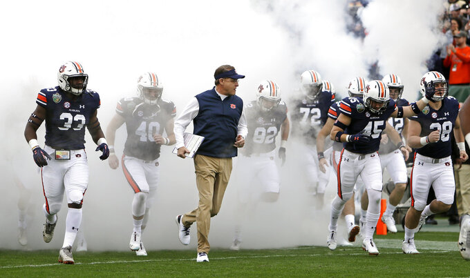 Auburn head coach Gus Malzahn, center, leads his team onto the field for the Music City Bowl NCAA college football game against Purdue Friday, Dec. 28, 2018, in Nashville, Tenn. (AP Photo/Mark Humphrey)