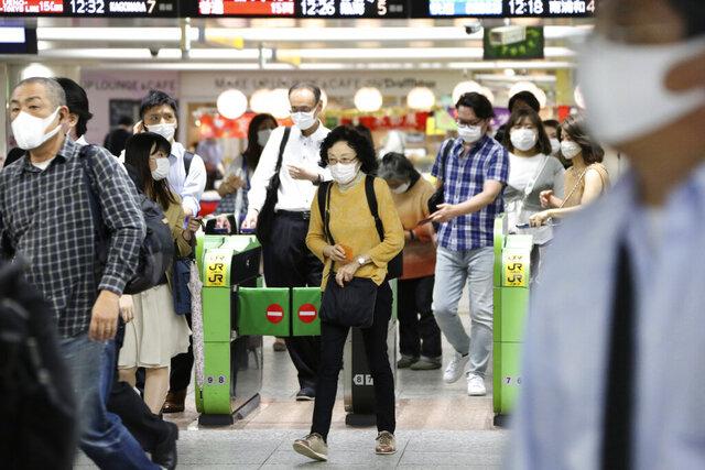 Passengers wearing face masks to protect against the spread of the new coronavirus walk through the gates at Yokohama station Tuesday, July 14, 2020. (AP Photo/Koji Sasahara)