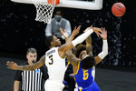 West Virginia's Gabe Osabuohien (3) blocks a shot by Morehead State's Skyelar Potter (5) during the second half of a college basketball game in the first round of the NCAA tournament at Lucas Oil Stadium Saturday, March 20, 2021, in Indianapolis. (AP Photo/Mark Humphrey)