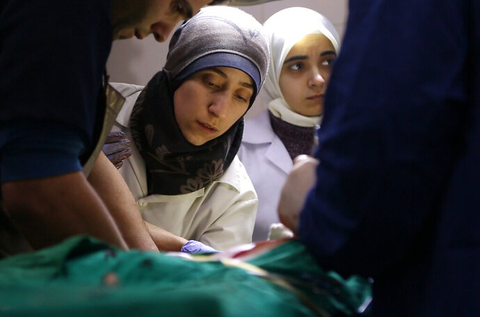 This image released by National Geographic shows Dr. Amani, center, in the operating room in Syria in a scene from the Oscar nominated documentary