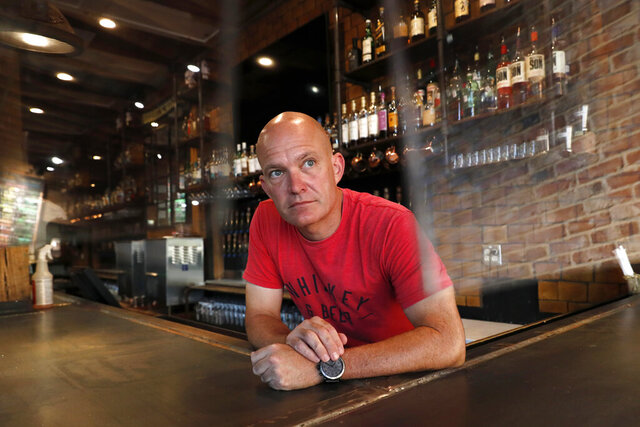 Jeff Brightwell, owner of Dot's Hop House, is framed between protective shielding placed over the bar as he poses for a photo at his establishment in the Deep Ellum entertainment district in Dallas, Thursday, Aug. 20, 2020. (AP Photo/Tony Gutierrez)