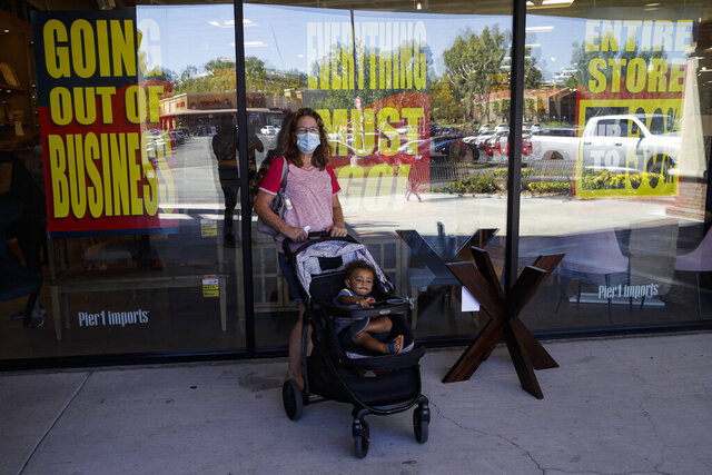 A shopper stands outside of a Pier 1 Imports store as going out of business signs are posted amid the coronavirus pandemic Wednesday, July 1, 2020, in Santa Clarita, Calif. (AP Photo/Marcio Jose Sanchez)