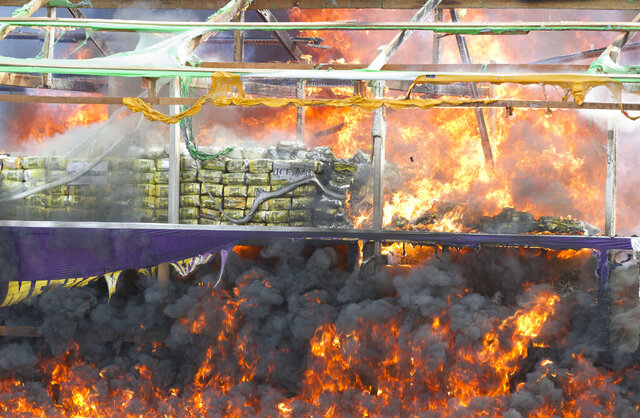 FILE: In this June 26, 2019, file photo, smoke and flames billow from burning narcotics during a destruction ceremony on the outskirts of Yangon, Myanmar. Narcotics police in Myanmar have seized a large amount of liquid fentanyl, providing the first evidence that the synthetic opioid is being produced in quantity in Southeast Asia's infamous Golden Triangle region. (AP Photo/Thein Zaw, File)