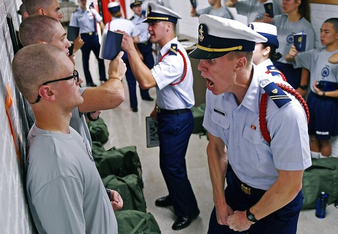 FILE - In this July 1, 2019, file photo, Whisky 2 company Cadre Jacob Denns, right, shouts instructions to swab Nicolas Fisher, left, of Pelham, N.H., during haircut and mailbox issue on the first day of a seven-week indoctrination to military academy life for the Class of 2023 at the U.S. Coast Guard Academy in New London, Conn. On Wednesday, Dec. 11, Congress will release results of an 18-month investigation into how the Coast Guard handles complaints of harassment and bullying, launched because of how complaints were dealt with at the Coast Guard Academy. (Sean D. Elliot/The Day via AP, File)