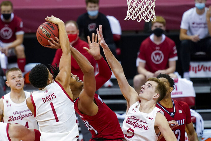 Wisconsin's Jonathan Davis (1) blocks a shot by Louisville's Jae'Lyn Withers (24) during the first half of an NCAA college basketball game Saturday, Dec. 19, 2020, in Madison, Wis. (AP Photo/Andy Manis)