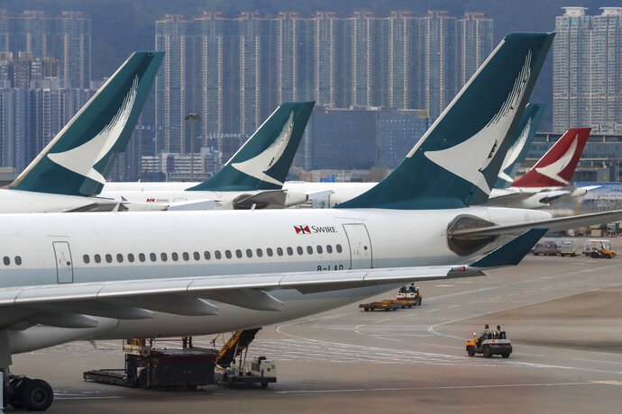 FILE - In this Aug. 12, 2019, file photo, ground crew drive past Cathay Pacific Airways planes park at the Hong Kong International Airport. Hong Kong airline Cathay Pacific says passenger traffic slumped last month on plummeting demand from mainland Chinese travelers. The carrier's September traffic figures released Friday, Oct. 18, are the latest sign that mainland visitors are staying away from the semiautonomous Chinese city as pro-democracy protests continue.(AP Photo/Vincent Thian, File)