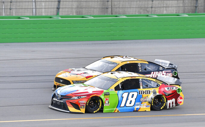 Kyle Busch (18) tries to fight off the pass attempt from Clint Bowyer (14) during the NASCAR Cup Series auto race at Kentucky Speedway in Sparta, Ky., Saturday, July 13, 2019. (AP Photo/Timothy D. Easley)