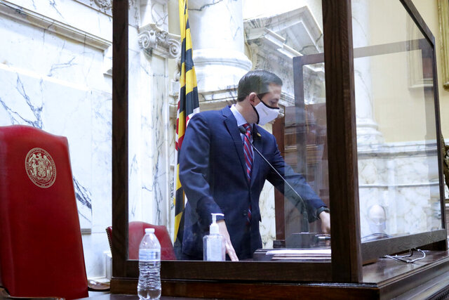 Senate President Bill Ferguson, a Baltimore Democrat, stands at the rostrum in the Maryland Senate on Thursday, Jan. 7, 2021 in Annapolis, Md. Precautions, including transparent panels, are being taken this year to help protect lawmakers as they gather for the annual 90-day legislative session, which begins Wednesday, Jan. 13. (AP Photo/Brian Witte)