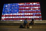 An Israeli couple sits near the Tel Aviv municipality building as it is lit up with the flag of the United States in Tel Aviv, Israel, Thursday, Jan. 7, 2021. Officials said the display is a sign of solidarity with the United States and support for democracy. (AP Photo/Sebastian Scheiner)