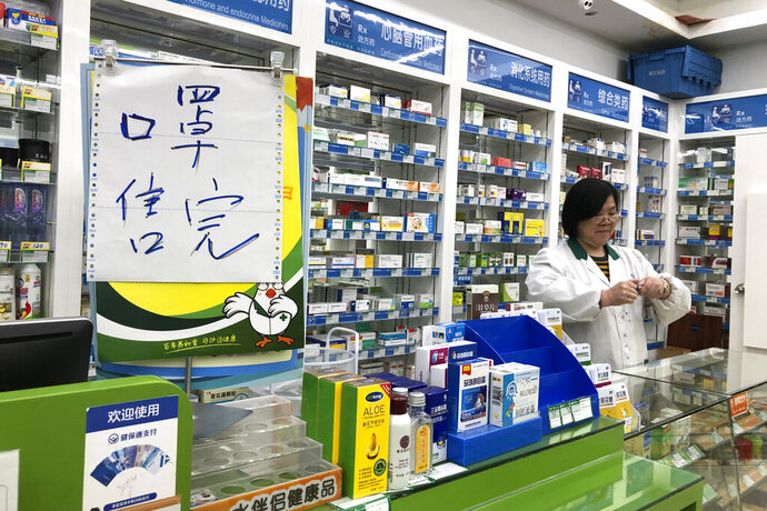 Pharmacist Liu Zhuzhen stands near a sign reading