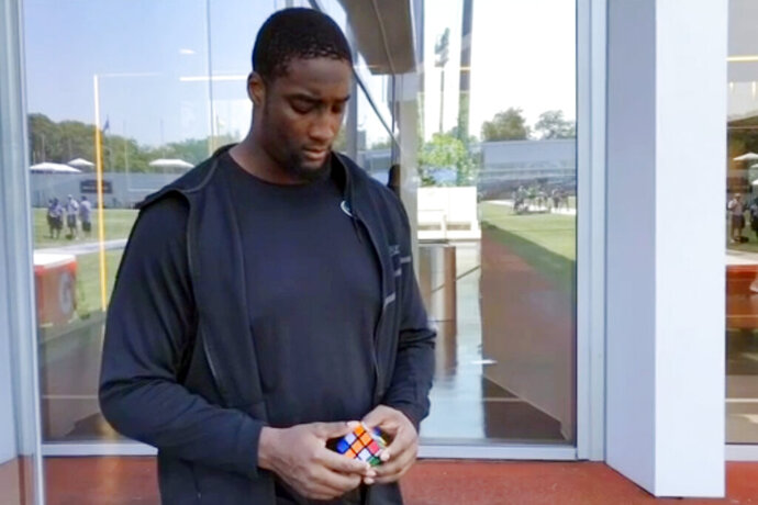 In this Sunday, July 28, 2019 image taken from video, offensive lineman Calvin Anderson, prepares to solve a Rubik's Cube behind his back at the New York Jets' NFL football practice facility in Florham Park, N.J. The Denver Broncos rookie offensive tackle has a knack for quickly solving a Rubik's Cube, even if it's behind his back or blindfolded. He's so good, in fact, that Rubik's Cube signed him this week as a brand ambassador , the first professional athlete to serve in that role. (AP Photo/Dennis Waszak)