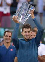 FILE - In this Sunday, March 17, 2019, file photo, Dominic Thiem, of Austria, foreground, raises a trophy over his head after defeating Roger Federer, of Switzerland, left, in the men's final at the BNP Paribas Open tennis tournament, in Indian Wells, Calif. Roger Federer has won one trophy so far in 2019, which puts him in a tie for the ATP lead, with 18 other players. That same sort of unprecedented parity is going on in the WTA, with 13 different champions from 13 tournaments.  (AP Photo/Mark J. Terrill, File)