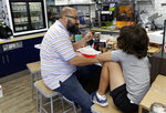 In this Tuesday, Aug. 14, 2018 photo, customer Julian Guilarte eats an empanada at the Mendez Fuel convenience store in Miami. There's no stale doughnuts and cold coffee at Mendez Fuel convenience store in Miami. Instead, customers can get their caffeine fix with an iced matcha and grab some vegan empanadas or an acai bowl for the road. (AP Photo/Lynne Sladky)
