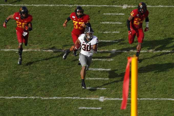 Oklahoma State running back Chuba Hubbard, center, breaks away from Iowa State's defense to score a touchdown during the first half of an NCAA college football game, Saturday, Oct. 26, 2019, in Ames, Iowa. (AP Photo/Matthew Putney)