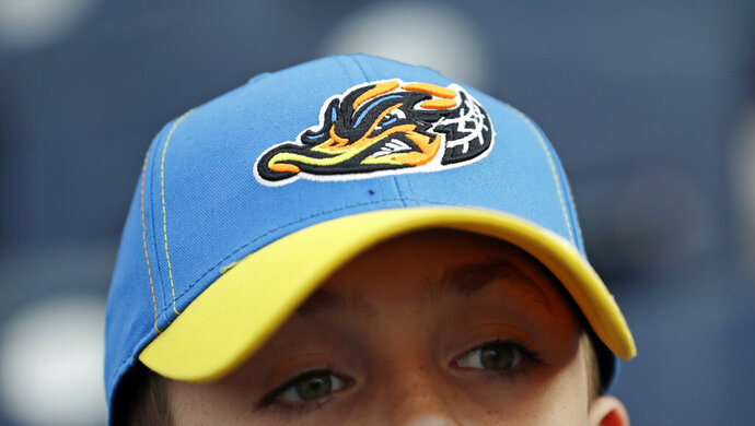"Jake Sheehan, 9, wears an Akron RubberDucks cap as he watches a minor league baseball game between Akron and the Bowie Baysox, Thursday, April 18, 2019, in Akron, Ohio. For Akron, whose history is intertwined with the rubber industry's, ""a tough, gritty duck that's really got that blue-collar ethos to it"" was an ideal choice to rebrand, for both adults and kids. (AP Photo/Tony Dejak)"