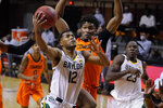 FILE - Baylor guard Jared Butler (12) goes to the basket in front of Oklahoma State forward Matthew-Alexander Moncrieffe, rear, in the first half of an NCAA college basketball game in Stillwater, Okla., in this Saturday, Jan. 23, 2021, file photo. Butler is The Associated Press Big 12 men's basketball player of the year and a member of the All-Big 12 first team, announced Tuesday, March 9, 2021. (AP Photo/Sue Ogrocki, File)