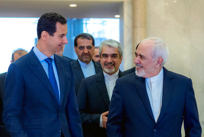 This photo released on the official Facebook page of Syrian Presidency shows Syrian President Bashar Assad, left, speaking with Iranian Foreign Minister Mohammad Javad Zarif, right, in Damascus, Syria, Tuesday, April 16, 2019. Zarif has blasted upon arrival in Syria the Trump administration decision to designate Tehran's Revolutionary Guards Corps a terrorist organization calling it a