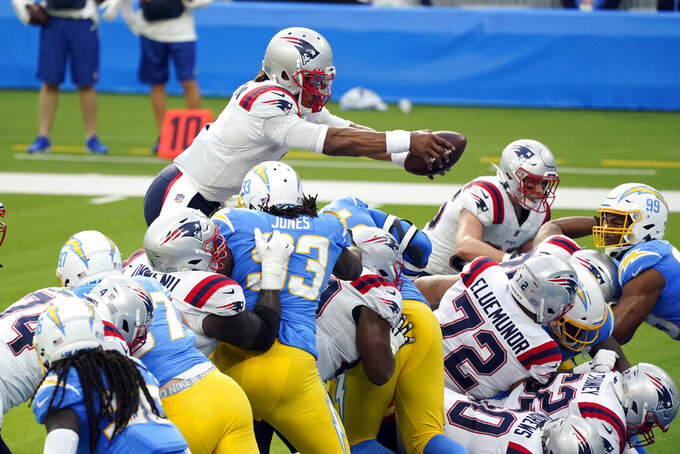 New England Patriots quarterback Cam Newton, top, jumps into the end zone for a touchdown during the first half of an NFL football game against the Los Angeles Chargers Sunday, Dec. 6, 2020, in Inglewood, Calif. (AP Photo/Ashley Landis)