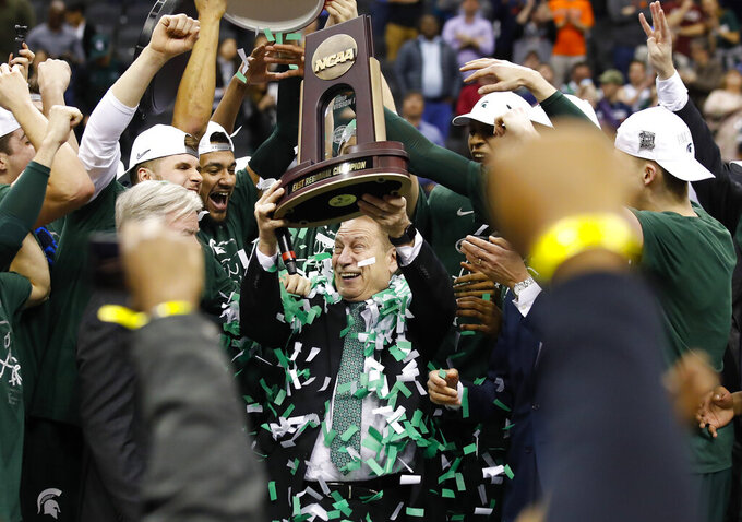 Michigan State head coach Tom Izzo holds up the NCAA men's East Regional Championship trophy after defeating Duke in a college basketball game in Washington, Sunday, March 31, 2019. Michigan State won 68-67. (AP Photo/Alex Brandon)