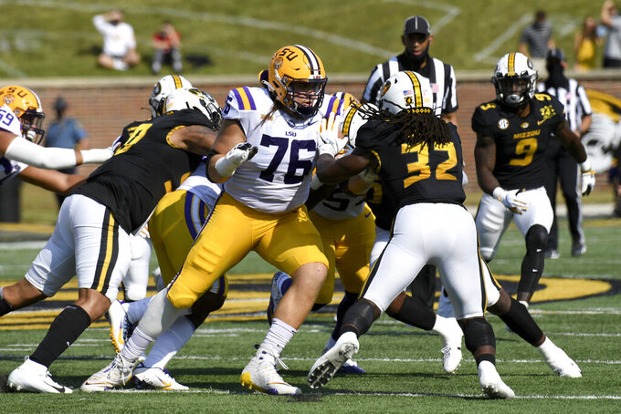 LSU offensive lineman Austin Deculus (76) blocks Missouri linebacker Nick Bolton (32) during the first half of an NCAA college football game against Missouri Saturday, Oct. 10, 2020, in Columbia, Mo. (AP Photo/L.G. Patterson)