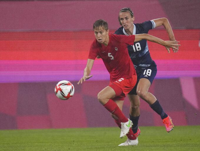 Canada's Quinn, left, and Britain's Jill Scott battle for the ball during a women's soccer match at the 2020 Summer Olympics, Tuesday, July 27, 2021, in Kashima, Japan. (AP Photo/Fernando Vergara)