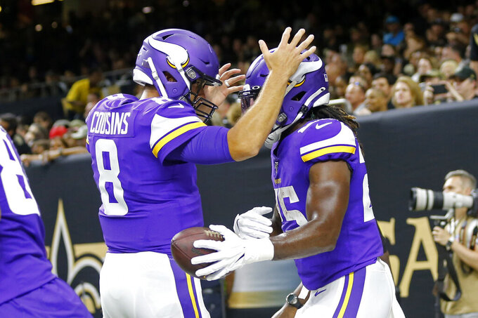 Minnesota Vikings quarterback Kirk Cousins (8) celebrates his touchdown pass to running back Alexander Mattison (25) in the first half of an NFL preseason football game against the New Orleans Saints in New Orleans, Friday, Aug. 9, 2019. (AP Photo/Gerald Herbert)