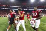 Nebraska quarterback Adrian Martinez (2) wipes his brow while leaving the field alongside Marquis Black (96) and Damion Daniels (93) following the team's 32-29 loss to Michigan in an NCAA college football game Saturday, Oct. 9, 2021, at Memorial Stadium in Lincoln, Neb. (AP Photo/Rebecca S. Gratz)