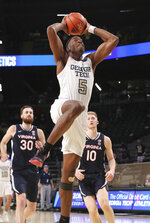 Georgia Tech forward Moses Wright gets past Virginia defenders Jay Huff, left, and Sam Hauser for a dunk during an NCAA college basketball game Wednesday, Feb. 10, 2021, in Atlanta. (Curtis Compton/Atlanta Journal-Constitution via AP)
