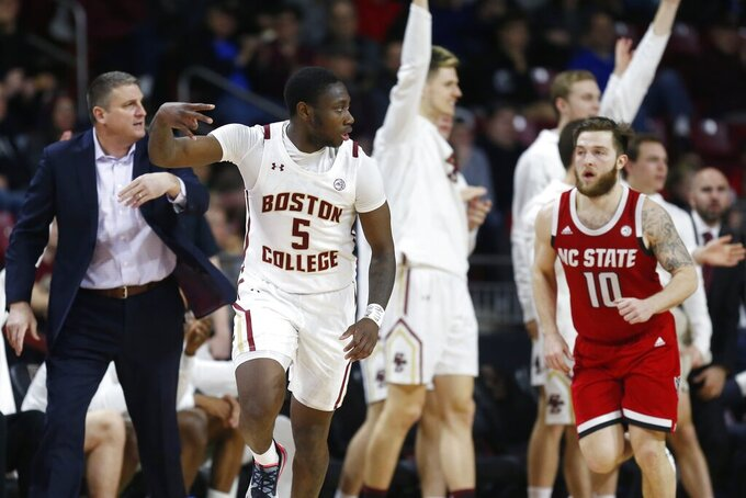 Boston College's Jay Heath (5) celebrates his three-point basket in front of head coach Jim Christian, left, and North Carolina State's Braxton Beverly (10) during the second half of an NCAA college basketball game in Boston, Sunday, Feb. 16, 2020. (AP Photo/Michael Dwyer)
